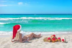 Beautiful blonde woman in bikini, red christmas hat and gift box Royalty Free Stock Photography