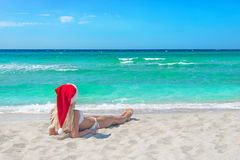 Beautiful blonde woman in bikini and red christmas hat on sea be Stock Images