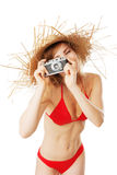 Beautiful blonde woman in bikini taking pictures. Isolated on white Stock Image