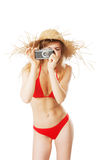 Beautiful blonde woman in bikini taking pictures. Isolated on white Stock Photography