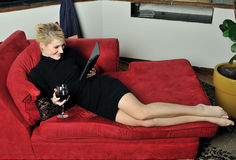 Beautiful blonde woman in black dress with wine Stock Images