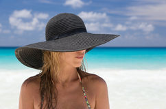Beautiful blonde woman with black hat, and tropical beach Stock Image