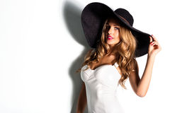 Beautiful blonde woman in black hat and white Royalty Free Stock Image
