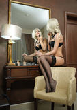 Beautiful blonde woman in black lingerie looking into mirror. Young beautiful woman in lingerie posing provocatively in hotel room Stock Images