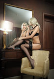 Beautiful blonde woman in black lingerie looking into mirror. Young beautiful woman in lingerie posing provocatively in hotel room Royalty Free Stock Photos