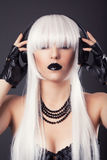 Beautiful blonde woman with black make-up and accessories listen Royalty Free Stock Photo
