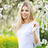Beautiful blonde woman in a blooming garden in spring Royalty Free Stock Images