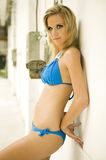 Beautiful blonde woman in blue bikini by a wall Royalty Free Stock Images