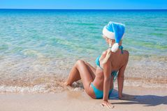 Beautiful blonde woman in blue christmas hat on sea beach. New y Royalty Free Stock Photography