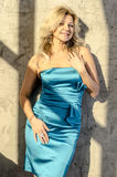 Beautiful blonde woman in a blue cocktail dress.  Royalty Free Stock Photography
