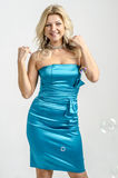 Beautiful blonde woman in a blue cocktail dress.  Royalty Free Stock Image