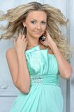 Beautiful blonde woman in a blue dress. Stock Images
