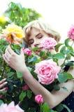 Beautiful blonde woman in blue dress  posing in garden Royalty Free Stock Image