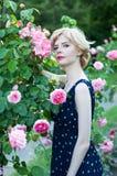 Beautiful blonde woman in blue dress  posing in garden Stock Photos