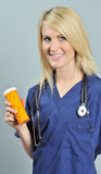 Beautiful blonde woman in blue scrubs - pills Royalty Free Stock Photos