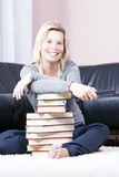 Beautiful blonde woman in the book is based on the remote contro Royalty Free Stock Photography