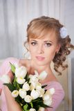 Beautiful blonde woman with a bouquet of tulips Stock Images