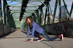 Beautiful blonde woman on a bridge with graffiti. Girl with long legs in blue jeans and sneakers doing sports on a bridge stock photo