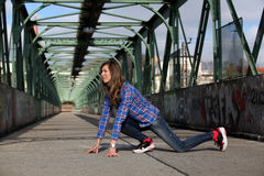 Beautiful blonde woman on a bridge with graffiti. Girl with long legs in blue jeans and sneakers doing sports on a bridge stock image