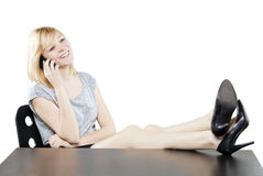 Beautiful blonde woman in business attire on the phone at desk Royalty Free Stock Photos