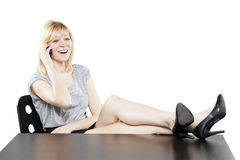 Beautiful blonde woman in business attire on the phone at desk Stock Photos