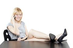 Beautiful blonde woman in business attire on the phone at desk Stock Photo