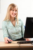 Beautiful blonde woman busy at office computer. Big smile from beautiful young blonde woman working in office looking at computer screen royalty free stock photography
