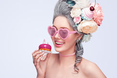 Beautiful blonde woman with a cake. Sweet sexy lady with heart glasses. Vintage style. Fashion photo Stock Image