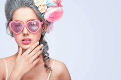Beautiful blonde woman with a cake. Sweet sexy lady with heart glasses. Vintage style. Fashion photo with copy space Royalty Free Stock Image