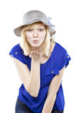 Beautiful blonde woman in casual attire with hat blowing a kiss. Against white background Stock Image