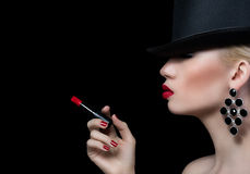 Beautiful blonde woman with cigarette and red lips. On black background Royalty Free Stock Photography