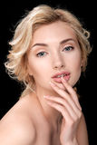 Beautiful blonde woman with clean skin. Finger touches lips. Stock Photos