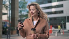 Beautiful blonde woman with coffee net surfing in the street. Beautiful blonde woman wearing beige coat and holding coffee to go net surfing on her smartphone in stock video footage
