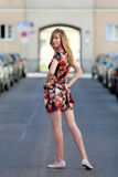 Beautiful blonde woman in a colorful summer dress. Woman looking over her shoulder on the street stock photo