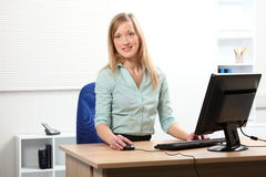 Beautiful blonde woman at computer in office Stock Photography
