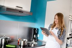 Beautiful blonde woman cooking dinner in the kitchen Royalty Free Stock Photos