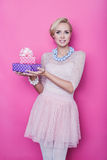 Beautiful blonde woman with cream colored dress holding pink and purple gift boxes Stock Photography