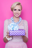 Beautiful blonde woman with cream dress giving colorful gift Stock Image