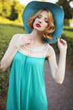 Beautiful blonde woman with curly short bob hairstyle, delicate. Make up and red lips in green short dress and a hat at the park. Fashion sensual posing on Stock Photography