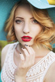 Beautiful blonde woman with curly short bob hairstyle, delicate. Make up and red lips in green short dress and a hat at the park. Fashion sensual posing on Stock Photos