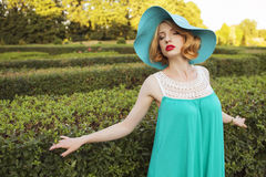 Beautiful blonde woman with curly short bob hairstyle, delicate. Make up and red lips in green short dress and a hat at the park. Fashion sensual posing on Royalty Free Stock Photos