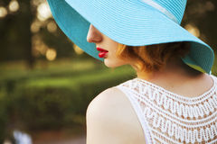 Beautiful blonde woman with curly short bob hairstyle, delicate. Make up and red lips in green short dress and a hat at the park. Fashion sensual posing on Royalty Free Stock Image