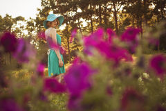 Beautiful blonde woman with curly short bob hairstyle, delicate. Make up and red lips in green short dress at the park. Fashion sensual posing on summer sunset Royalty Free Stock Photos