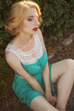 Beautiful blonde woman with curly short bob hairstyle, delicate. Make up and red lips in green short dress at the park. Fashion sensual posing on summer sunset Stock Photo