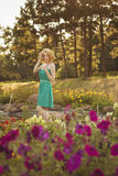 Beautiful blonde woman with curly short bob hairstyle, delicate. Make up and red lips in green short dress at the park. Fashion sensual posing on summer sunset Royalty Free Stock Image