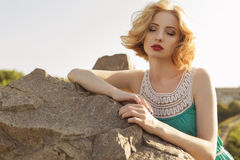 Beautiful blonde woman with curly short bob hairstyle, delicate. Make up and red lips in green short dress at the park. Fashion sensual posing on summer sunset Stock Photography