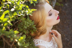 Beautiful blonde woman with curly short bob hairstyle, delicate. Make up and red lips in green short dress at the park. Fashion sensual posing on summer sunset Stock Images