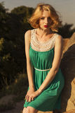 Beautiful blonde woman with curly short bob hairstyle, delicate. Make up and red lips in green short dress at the park. Fashion sensual posing on summer sunset Royalty Free Stock Photography