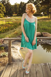 Beautiful blonde woman with curly short bob hairstyle, delicate. Make up and red lips in green short dress at the park. Fashion sensual posing on summer sunset Stock Image