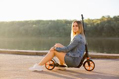 Beautiful blonde woman in denim clothes sits on her scooter and smiles at the camera on the waterfront street royalty free stock photography